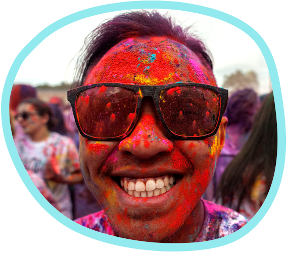 a student covered in a rainbow of powder smiles at the camera after a ceremony marking the Hindu festival of Holi