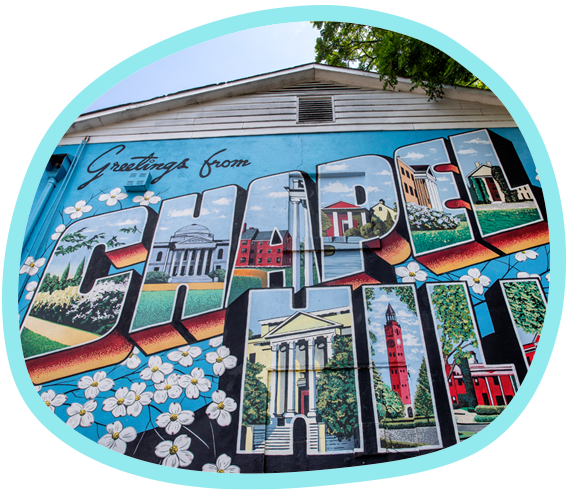 A painted mural on the outside of a building with dogwood flowers and the words Greetings from Chapel Hill