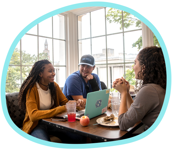 Three students share a meal at a dining table in Carolina's Lenoir Dining Hall