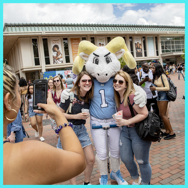 Two students pose for a photo with Rameses.