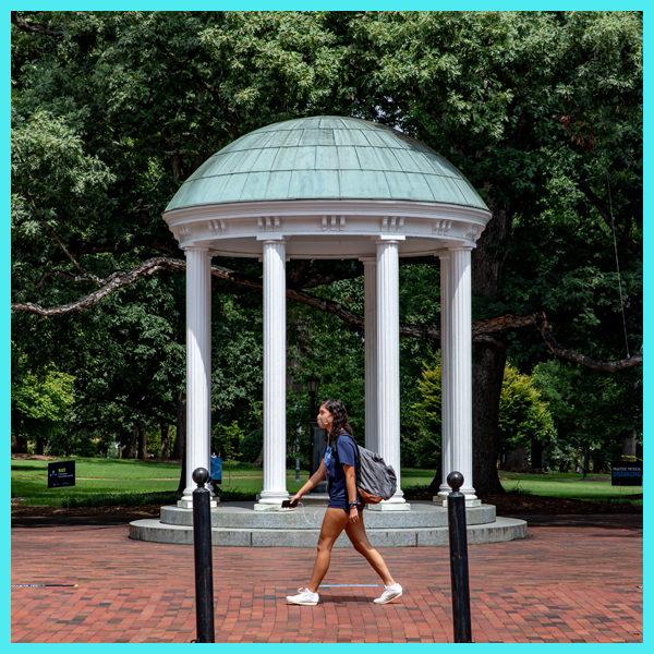 Student wearing mask walks past the Old Well.