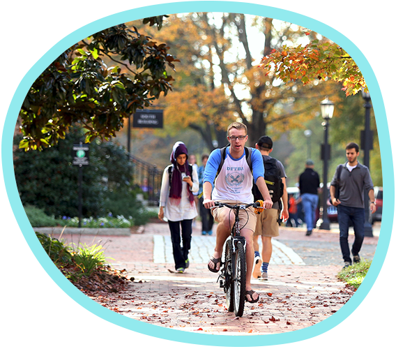 A student rides his bike down a brick sidewalk on Carolina's campus