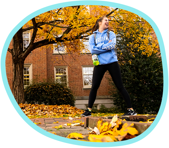 a student walking past a fall tree with yellow leaves looks back over her shoulder while laughing