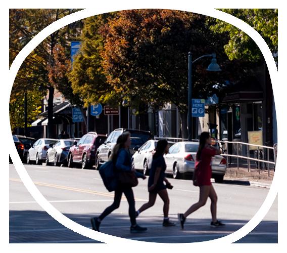 Students in shadow walk in a crosswalk on Franklin Street in Chapel Hill