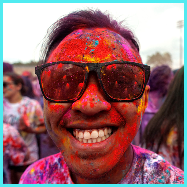 A smiling student covered in colored powder at UNC's Holi Moli event.