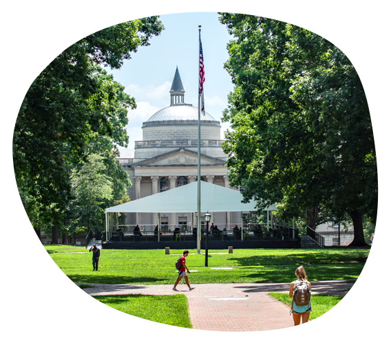 students walk across Carolina's quad on a sunny day with a flag pole and the domed roof of Wilson Library in the background
