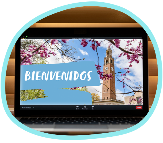 A laptop screen shows an image of Carolina's Bell Tower surrounded by flowering tree branches and the word bienvenidos