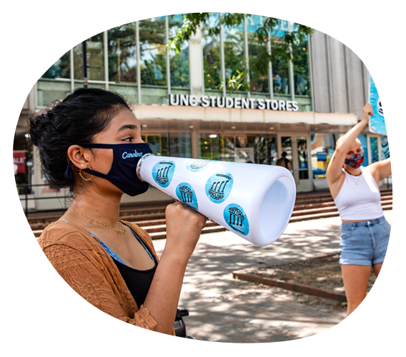 two students stand in front of the UNC Student Stores building and with a sign and a megaphone work to grab the attention of other students