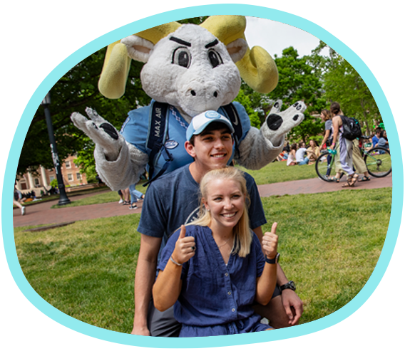 Carolina's Rameses mascot makes a shoulder shrugging gesture while posing behind two students smiling and giving two thumbs-up