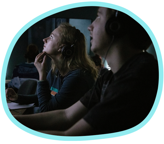 two students sit in a darkened room looking at a screen that illuminates their faces