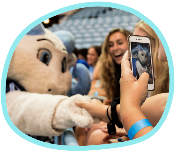 a student takes a picture of Carolina's Rameses mascot on her phone while smiling friends look on