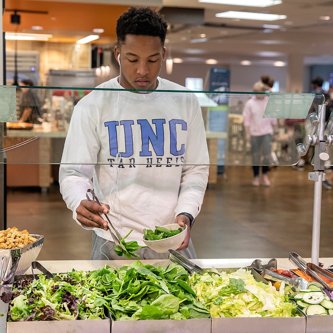 a student serves himself a salad at a buffet in Carolina's dining hall