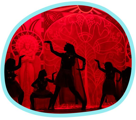 students dressed in Egyptian pharaoh outfits move across a stage, silhouetted against a bright red backdrop