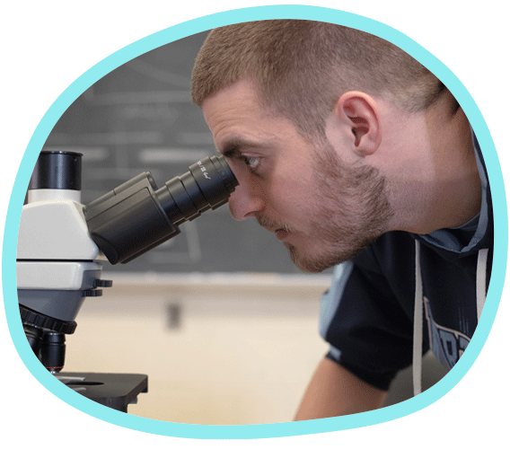 a student looks through a microscope in a Comparative Physiology class at Carolina