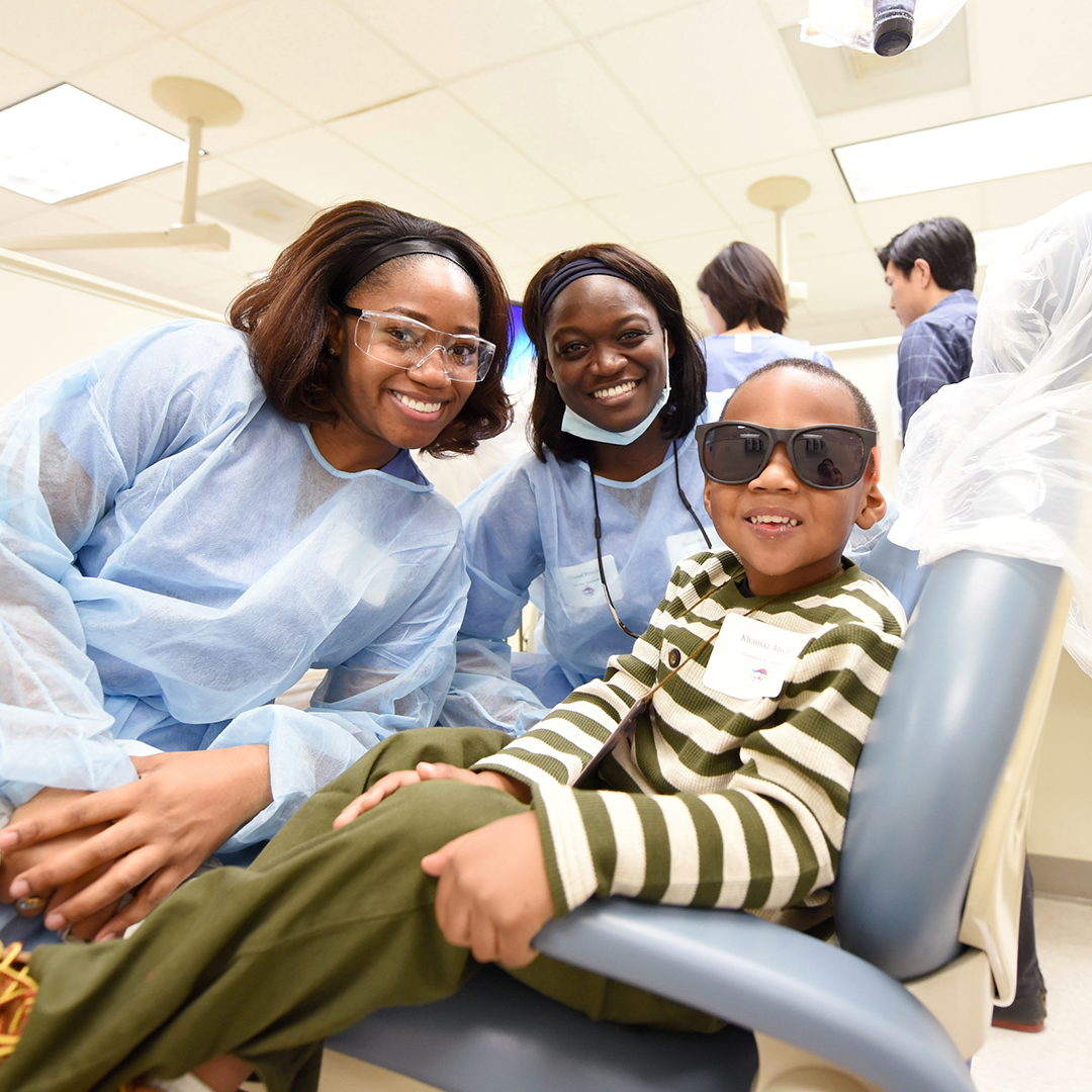 two dental students pose and smile with a boy receiving dental care at UNC-Chapel Hill