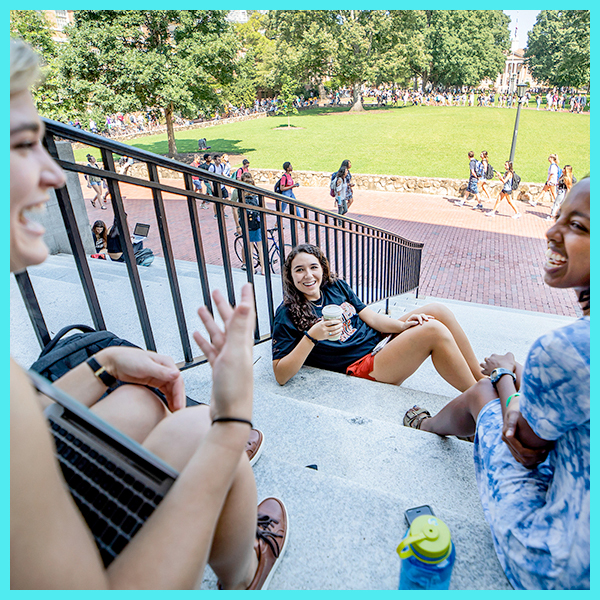 Students hang out on the steps of Wilson Library.